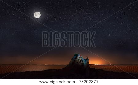 Moon And Stars Over Stone In Desert
