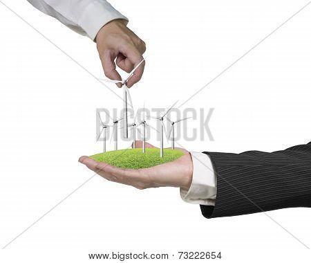 Men Hands Holding Windturbines On Grass