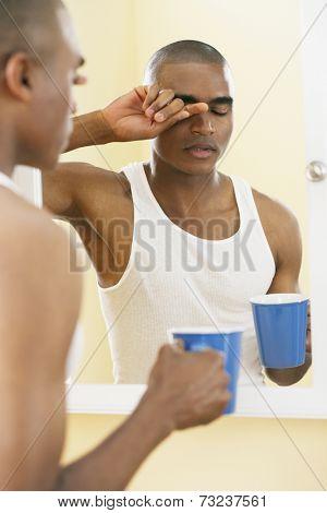 African man rubbing eyes