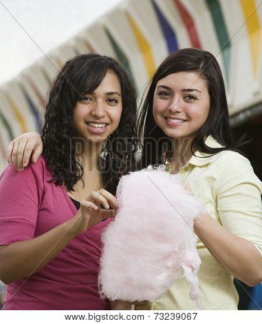 Multi-ethnic teenaged girls eating cotton candy