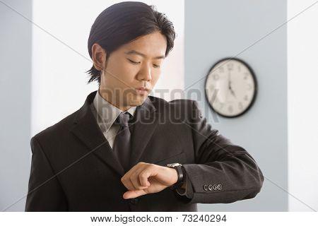 Asian businessman looking at wristwatch