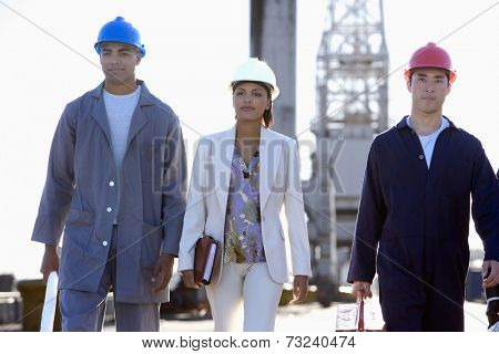 Multi-ethnic businesswoman and construction workers walking