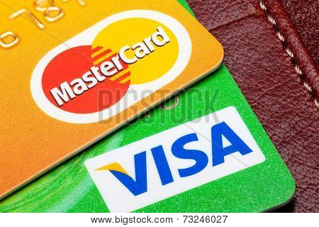 Estonia - September 24, 2014. Visa and Mastercard credit cards with the leather wallet on the background. Mastercard and Visa are the biggest credit card companies in the world.