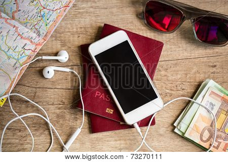Preparation for travel, cell phone, money, passport, road map on wooden table