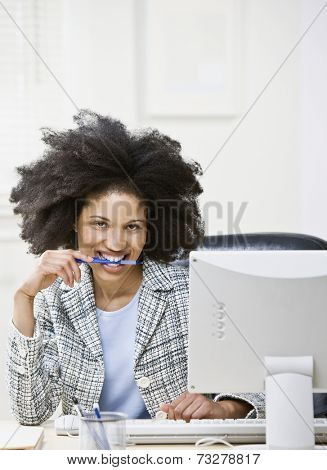 African American businesswoman biting on pen