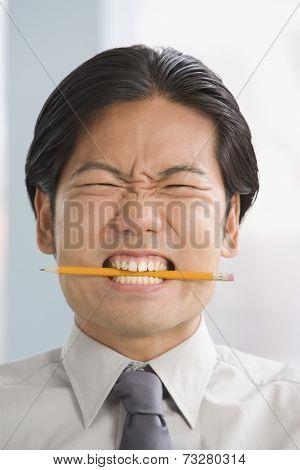 Asian businessman biting on pencil