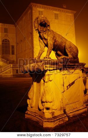 Architectural detail of a late Renaissance castle in Guarene northern Italy. A stone dog guards the entrance to the mansion.