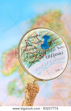 Blue tack on map of Scandinavia with magnifying glass looking in on Helsinki Finland poster