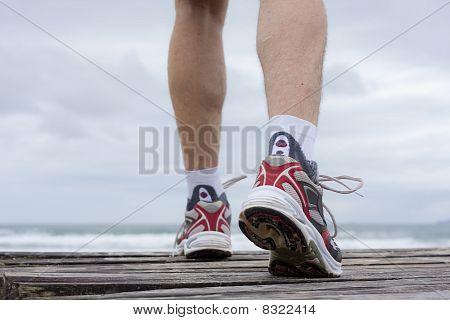 Feet Of Runner On A Beach