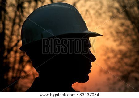 Silhouette of a mining labor against strong back light. Outlines of face with safety helmet. poster