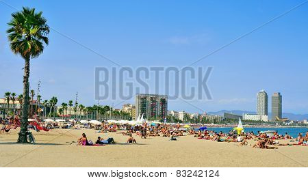 BARCELONA, SPAIN - AUGUST 19: Bathers in La Barceloneta Beach on August 19 2014 in Barcelona, Spain. This popular beach hosts about 500,000 visitors from everywhere during the summer season