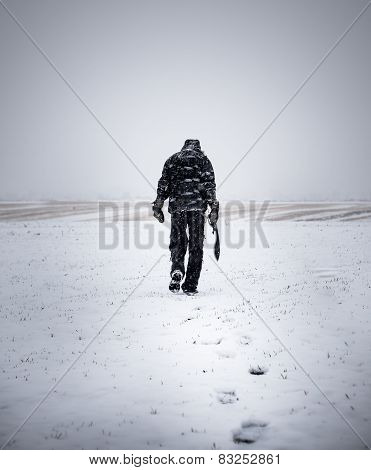 A man with a large knife walking wasteland