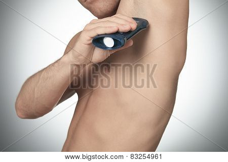 A Man uses deoderant on studio gray background
