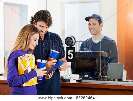 Mid adult couple holding snacks while buying movie tickets at box office
