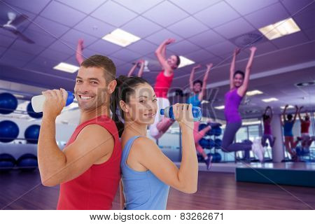 Composite image of fit man and woman smiling at camera together
