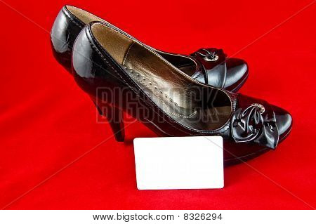 black shoes and card on red background