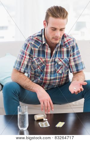 Hungover man with his medicine laid on coffee table at home in the living room
