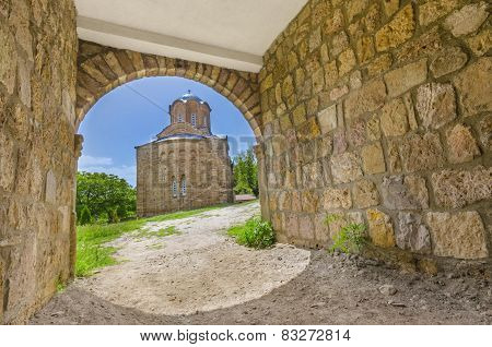 View of an ancient church through stone caved tunnel