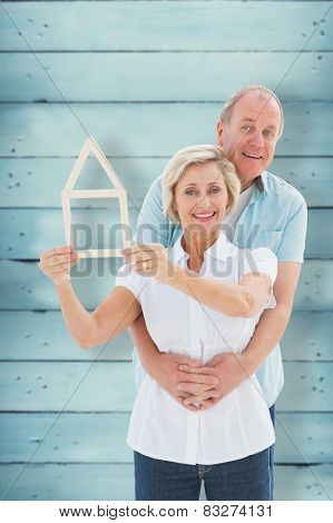 Happy older couple holding house shape against wooden planks poster