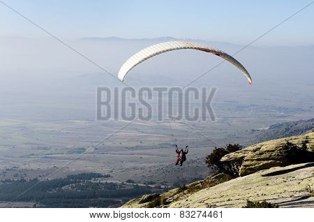 Paraglider taking off from a rocky mountain