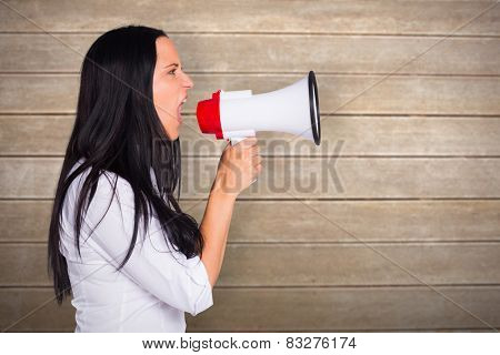 Young woman shouting through megaphone against wooden surface with planks