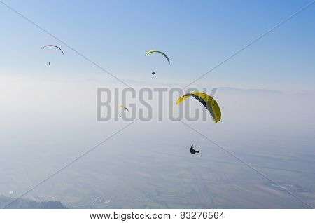 Paragliders against clear blue sky, extreme sport