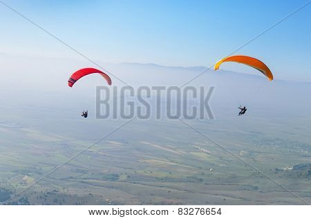 Paragliding high above the fields, extreme sport