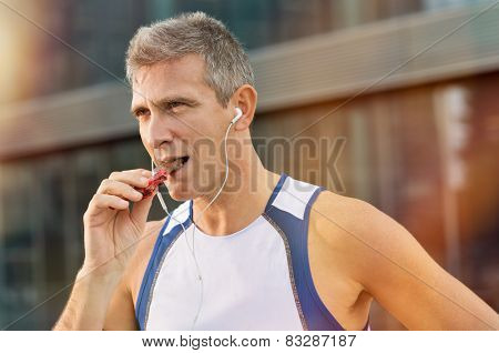 Portrait Of Fitness Mature Man Eating A Energy Bar Of Chocolate