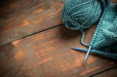 Woollen thread and knitting needle on wooden background poster
