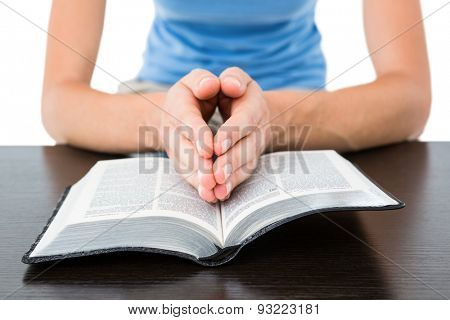 Woman praying while reading bible on white background