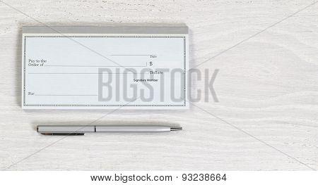Blank Checkbook And Silver Pen On White Desktop