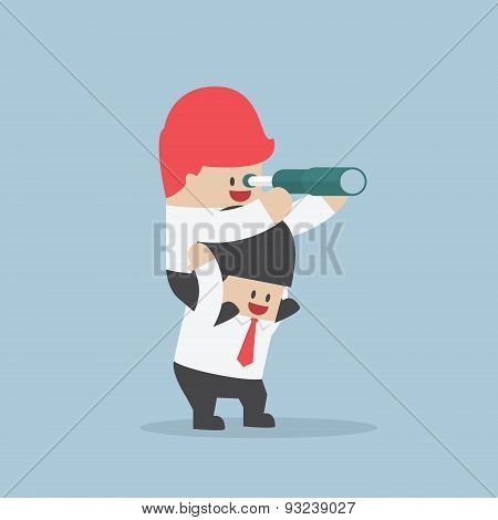 Businessman Riding On His Friend's Shoulder And Looking Through Spyglass