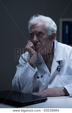 Older bored doctor with burnout sitting in office poster