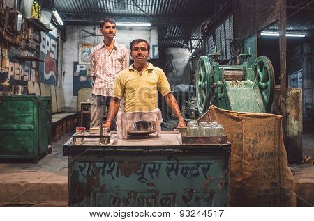 JODHPUR, INDIA - 17 FEBRUARY 2015: Vendor makes sugarcane juice in specialised machine. Finished juice is stored and covered with cotton rag. Post-processed with grain and texture.