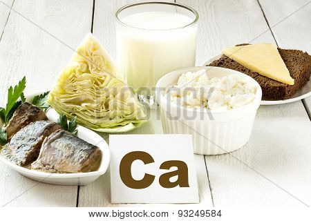 Foods rich in calcium (sardines in oil cabbage milk cottage cheese brown bread cheese) on white wooden table poster