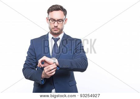 Serious businessman looking at his wristwatch