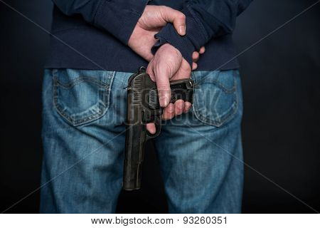 Close Up Of The Rear View Of The Person Who Holds A Hand Gun.