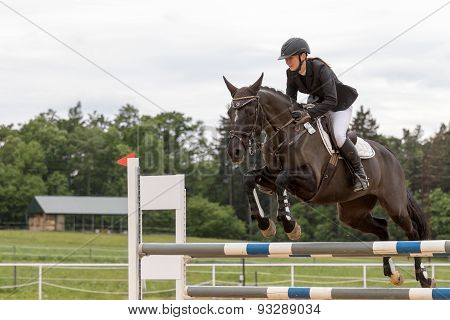 Young Horsewoman Is Jumping On Dark Brown Horse