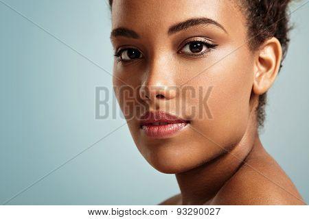 Pretty Black Woman's Closeup Portrait. Blue Background