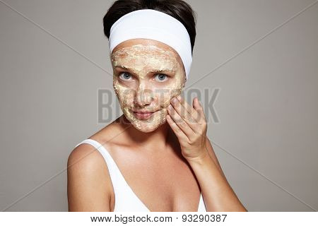 Woman Is Wondering And Touching Her Face With A Facial Mask