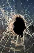 hole smashed in thickdirty glass with dark background poster