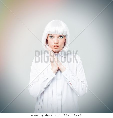 Portrait of beautiful smiling young woman in blonde wig and shirt over white background