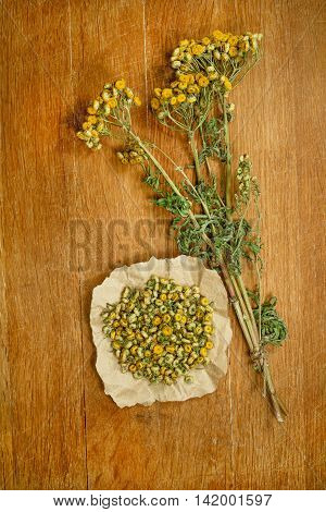 Tansy.Dried herbs for use in alternative medicine.Herbal medicine phytotherapy medicinal herbs.For preparation of infusions decoctions tinctures powders ointments tea.Background wooden board