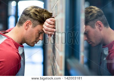 Stressed man leaning on wall in building