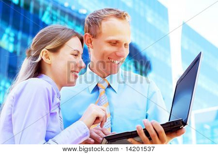 Happiness businessmans withlaptop on blur business architecture background