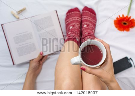 Woman Reading A Book And Having Cup Of Tea