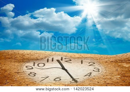 conceptual image of clock on dried cracked landscape over sky.