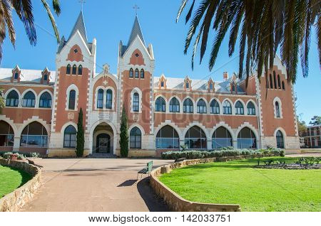 NEW NORCIA,WA,AUSTRALIA-JULY 15,2016: Grandiose St. Gertrude's Ladies College brick exterior with spanish gothic architecture under a blue sky with palm tree branches in the monastic town of New Norcia, Western Australia.