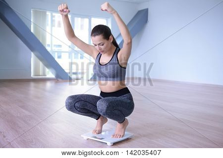 Woman celebrating a weightloss goal achievement on a scale at home
