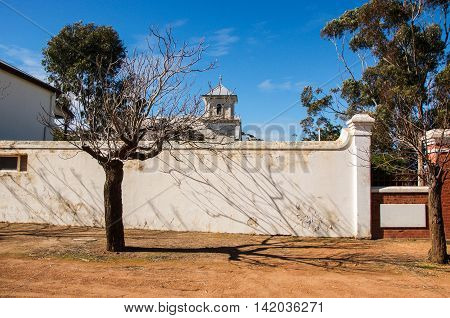 NEW NORCIA,WA,AUSTRALIA-JULY 15,2016: The Benedictine Monastery boundary wall with tree and shadow in the historic monastic town of New Norcia, Western Australia.